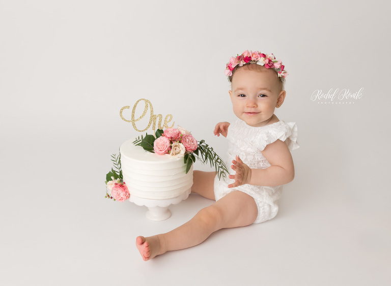 Little girl with lots of flowers getting ready to cake smash, cake smash photography