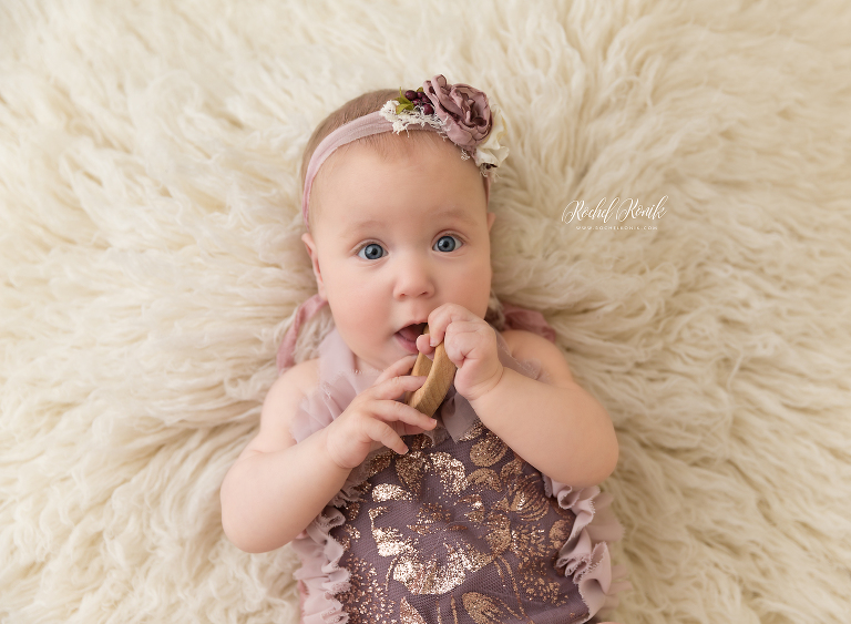 Little girl on her back with a teething ring, baby photography