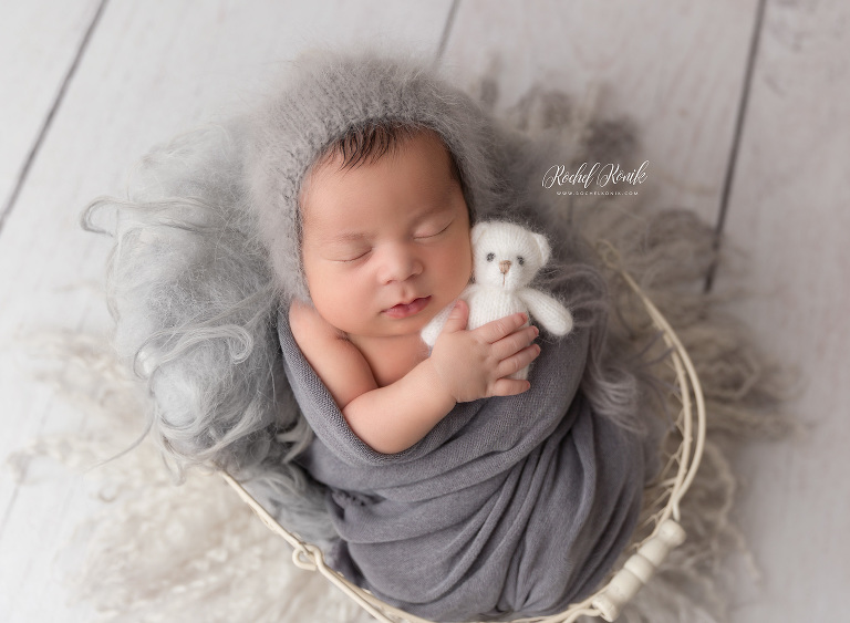 Baby sleeping with a little bear on gray background, newborn photography